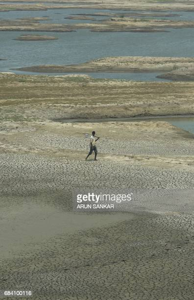 An Indian man walks over the parched bed of a reservoir on the outskirts of Chennai on May 17 2017 / AFP PHOTO / ARUN SANKAR