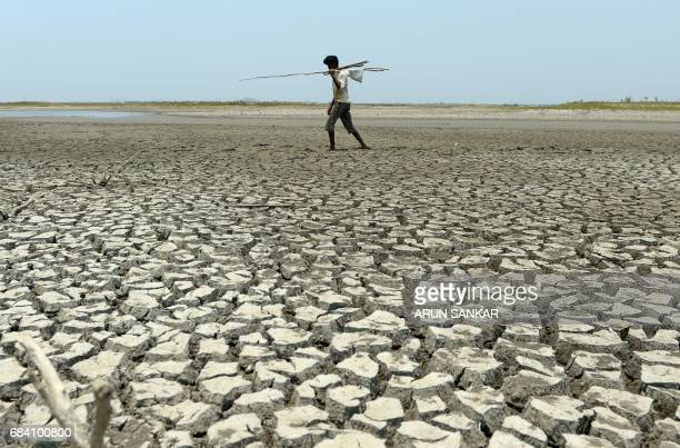 TOPSHOT An Indian man walks over the parched bed of a reservoir on the outskirts of Chennai on May 17 2017 / AFP PHOTO / ARUN SANKAR