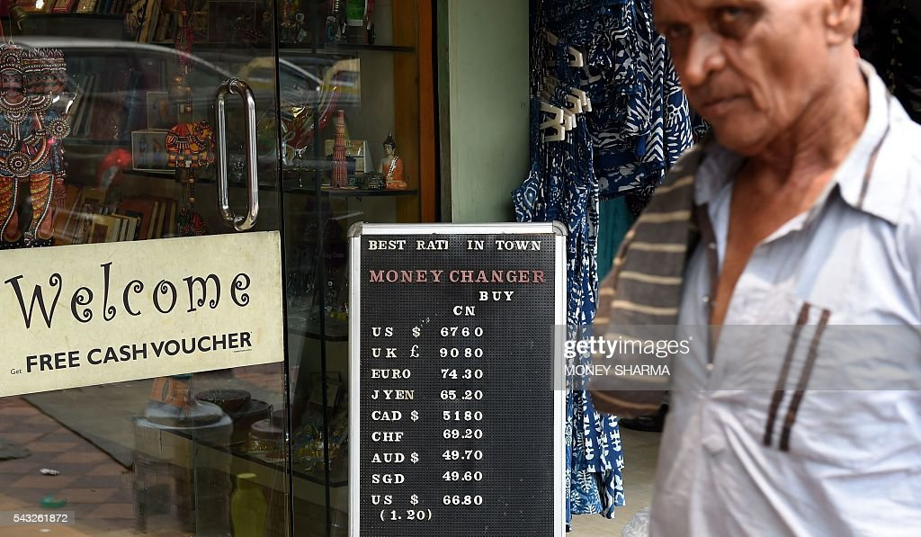 An Indian man walks past a board displaying currency exchange rates outside a shop in New Delhi on June 27, 2016. The pound sank on June 27 to 30-year lows while most stock markets tumbled following Britain's decision to leave the European Union, with traders fearing it will lead to months of uncertainty. / AFP / MONEY