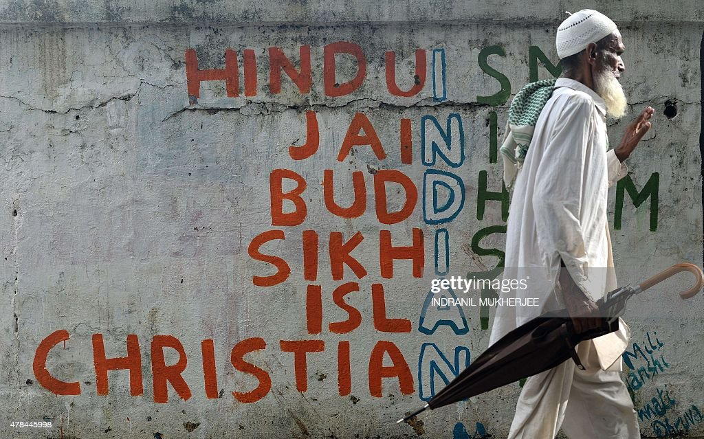 An Indian man walks past a wall graffiti on various religions in Mumbai on June 25 2015 AFP PHOTO/ Indranil MUKHERJEE