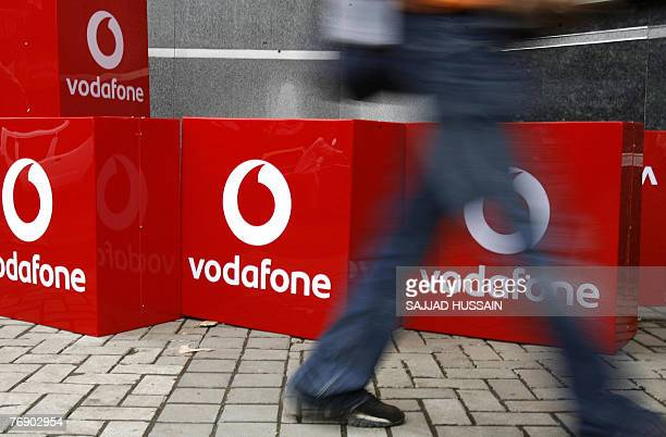 An Indian man walks past the signboard of telecom firm 'Vodafone' outside the corporate office in India's financial capital Mumbai 20 September 2007...