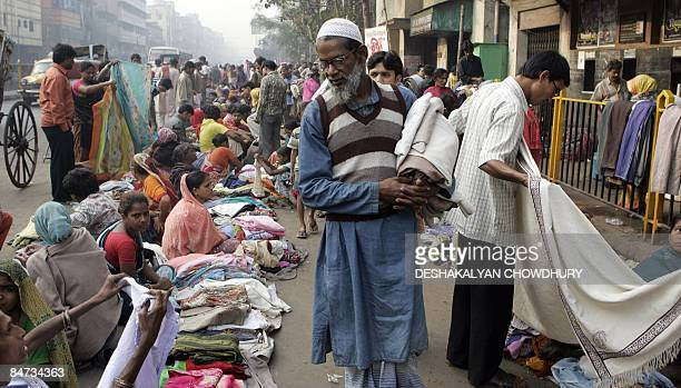 An Indian man walks past with his purchases as bargain hunters browse through clothing at a second hand clothing market in Kolkata on February 11...