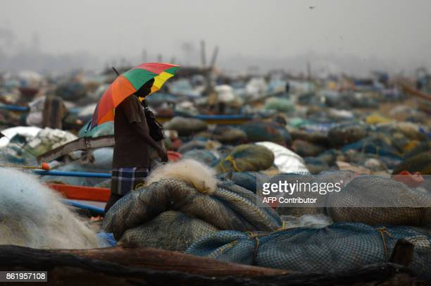 An Indian man walks under an umbrella amid rain near a fisherman's shanty at Pattinapakkam beach in Chennai on October 16 2017 / AFP PHOTO / ARUN...