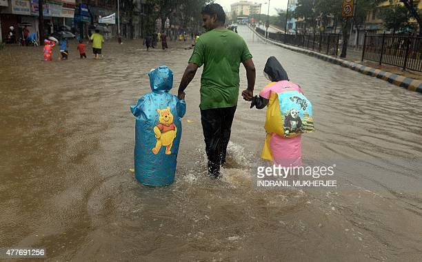 An Indian man walks with his children as they negotiate a waterlogged street in Mumbai on June 19 2015 Heavy monsoon showers lashed India's financial...