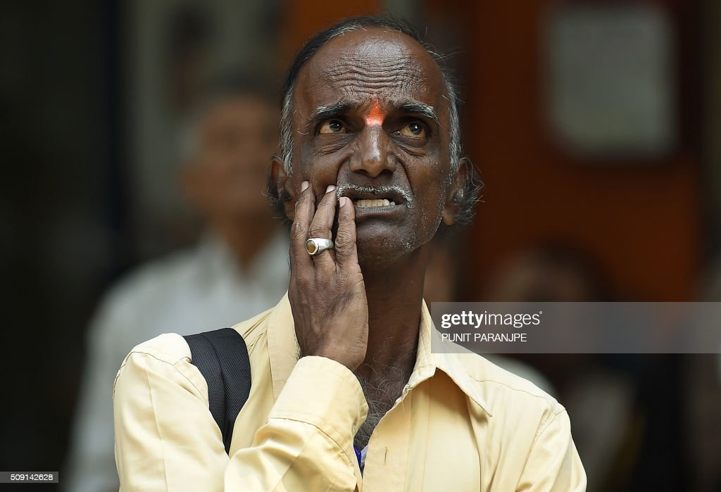An Indian man watches stock prices on a digital broadcast on the facade of the Bombay Stock Exchange (BSE) building in Mumbai on February 9, 2016. Asian stocks plunged across the board on February 9, the dollar dived against the yen, gold jumped and yields on Japanese government bonds fell to zero as fears about the global economy sent investors scrambling to safety. AFP PHOTO / PUNIT PARANJPE / AFP / PUNIT PARANJPE