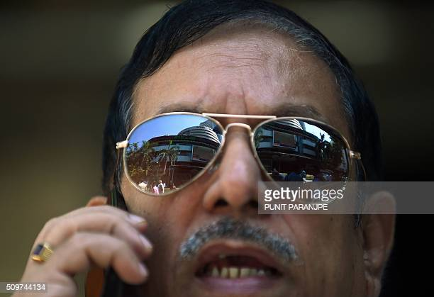 An Indian man watches stock prices on a digital broadcast on the facade of the Bombay Stock Exchange building in Mumbai on February 12 2016 A more...