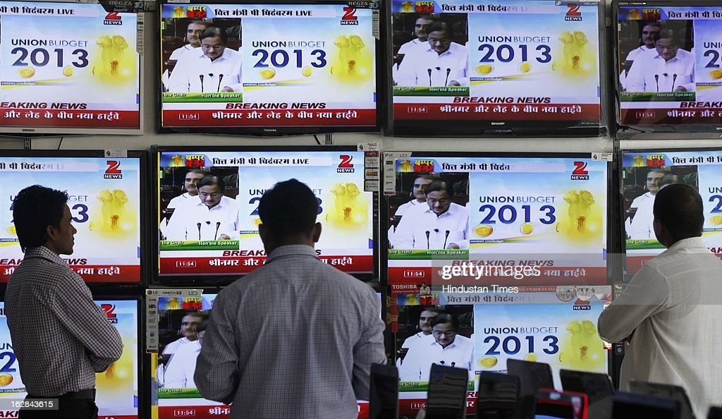An Indian man watches televisions broadcasting India's finance minister Palaniappan Chidambaram presenting the national budget in parliament on February 28, 2013 in Mumbai, India. Chidambaram Thursday unveiled a national budget with a promise to put Asia's third largest economy back on a path of high growth and to trim the fiscal deficit.