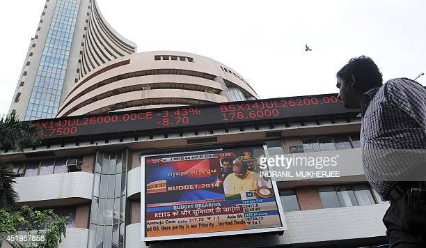 An Indian man watches the share prices ticker alongside a digital broadcast of Indian Finance Minister Arun Jaitley delivering his Budget speech at...