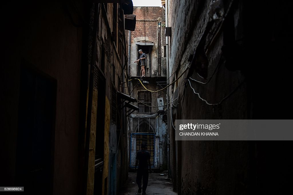 An Indian man waters the alley from the rooftop of his house in the old quarters of New Delhi on May 5, 2016. / AFP / CHANDAN