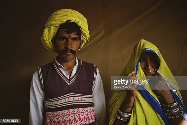 An Indian man wearing a brightlycoloured turban stands alongside his wife whose dressed in a matching coloured shawl during the Pushkar Fair near the...