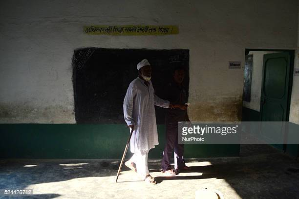 An indian man with his grandfather moves for casting their vote for first phase of Panchayat elections at a polling centrein Rampur23 kms from...