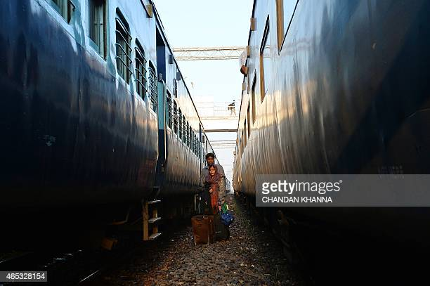 An Indian married couple stand with their luggage in a gap between moving trains as they wait to cross the railway tracks during a visit to their...
