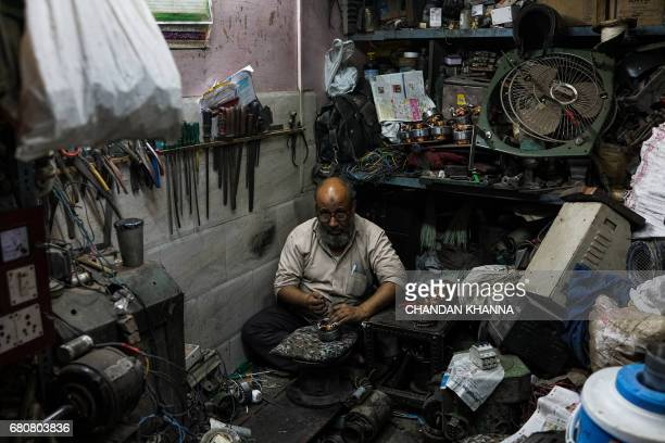 An Indian mechanic works in his workshop in the old quarters of New Delhi on May 9 2017 / AFP PHOTO / CHANDAN KHANNA