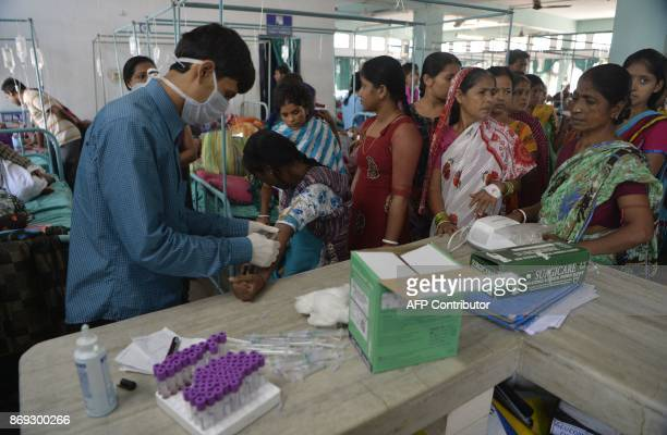 An Indian medical assistant collects blood samples from patients undertaking treatment for viral infections including dengue fever at Siliguri...