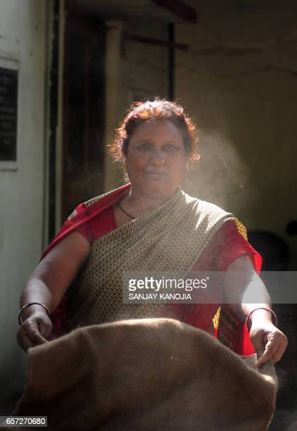 An Indian member of staff shakes dust from a floor mat at Civil Lines police station in Allahabad on March 24 2017 The recently elected Chief...
