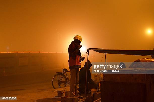 An Indian Metro construction labour drinks tea at a roadside makeshift tea stall on a cold and foggy morning in New Delhi on December 29 2014 The...