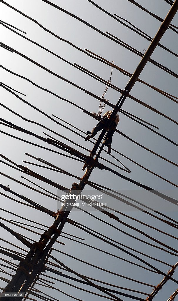 An Indian migrant labourer balances on a makeshift bamboo scaffolding in Mumbai on January 28, 2013. Migrant labourers from adjoining cities and states come to India's commercial capital in search of a livelihood as the city is seeing record levels of expansion and is still considered to be an oasis for potential job-seekers.