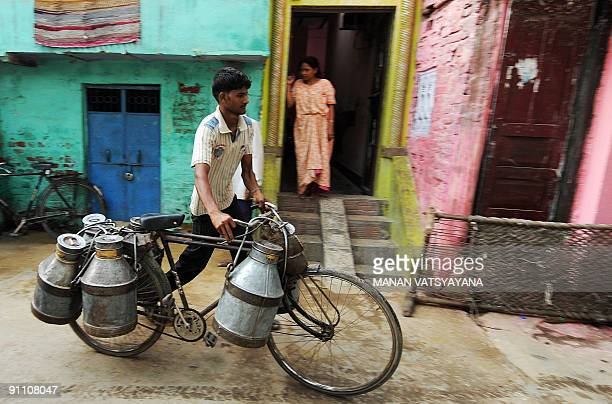 An Indian milkman carries canisters on his bicycyle in a local neighbourhood in New Delhi on September 24 2009 A large portion of the Indian...