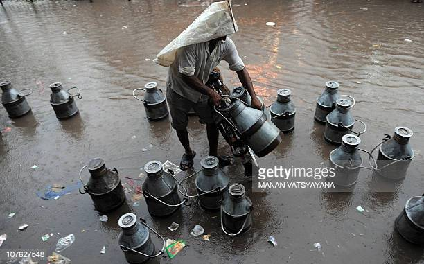 An Indian milkman covers his head with a plastic sheet as he carries milk cans during heavy rainfall in New Delhi on September 10 2009 Over 13mm of...