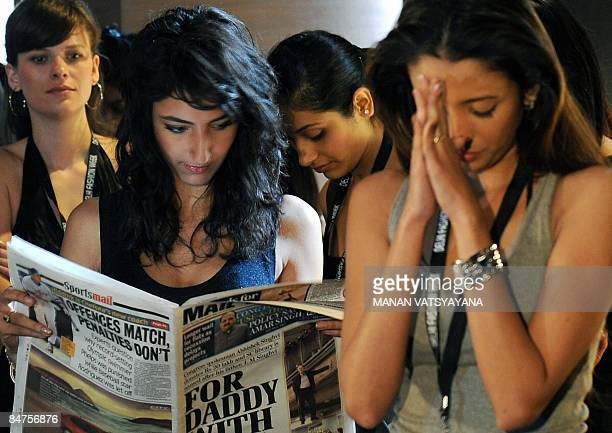 An Indian model reads a newspaper while waiting for her turn during auditions for the upcoming Delhi Fashion Week in New Delhi on February 12 2009...