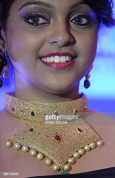 An Indian model showcases gold jewellery during the announcement of the sixth edition of the Hyderabad Jewellery Pearl and Gem Fair at a press...