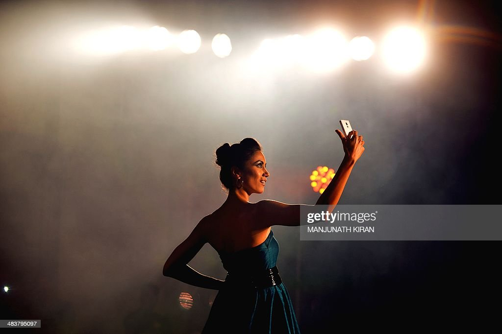 An Indian model showcases the new Samsung 'Galaxy S5' smartphone during a fashion show held as part of a consumer event in Bangalore on April 10, 2014. The phone along with its wearable 'Gear 2' will be available on sale across India from April 11, works on a firstime, True OctaCore Proccesor. AFP PHOTO/Manjunath KIRAN