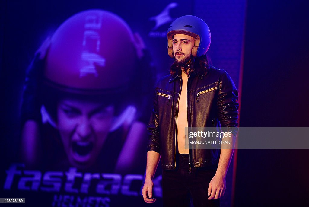 An Indian model wears a Fastrack motorcycle helmet at a fashion show during the launch in Bangalore on December 3, 2013. Fastrack, a youth accessories brand of Titan Industries Limited, launched helmets manufactured in India in technical collaboration with Italy's AGV brand helmets. AFP PHOTO/Manjunath KIRAN