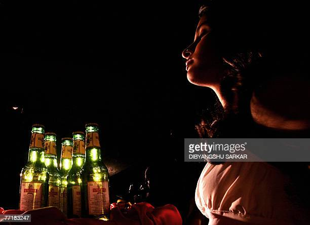 An Indian models gestures as she holds bottles of Kingfisher beer during the launch of commemorative packs of 'Indian October Fest' beer bottles in...