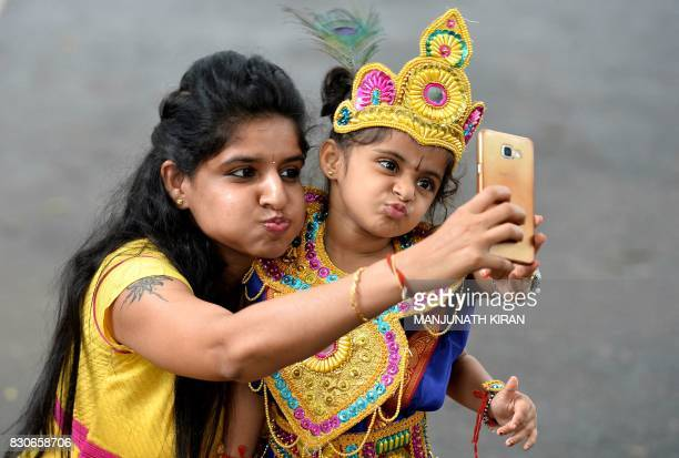 An Indian mother takes a selfie with her child dressed as the Hindu deity Krishna after an enactment competition as part of Krishna Janmashtami...