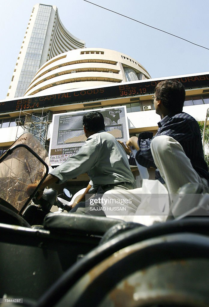An Indian motorcyclist and his passenger watch the live ticker showing the Bombay Stock Exchange (BSE) 30 share index (Sensex) on the BSE in Mumbai, 28 February 2007. Indian share prices fell 2.38 percent in morning trade 28 February in line with a wave of selling that has swept global markets on fears of a US economic slowdown, dealers said. AFP PHOTO/Sajjad HUSSAIN