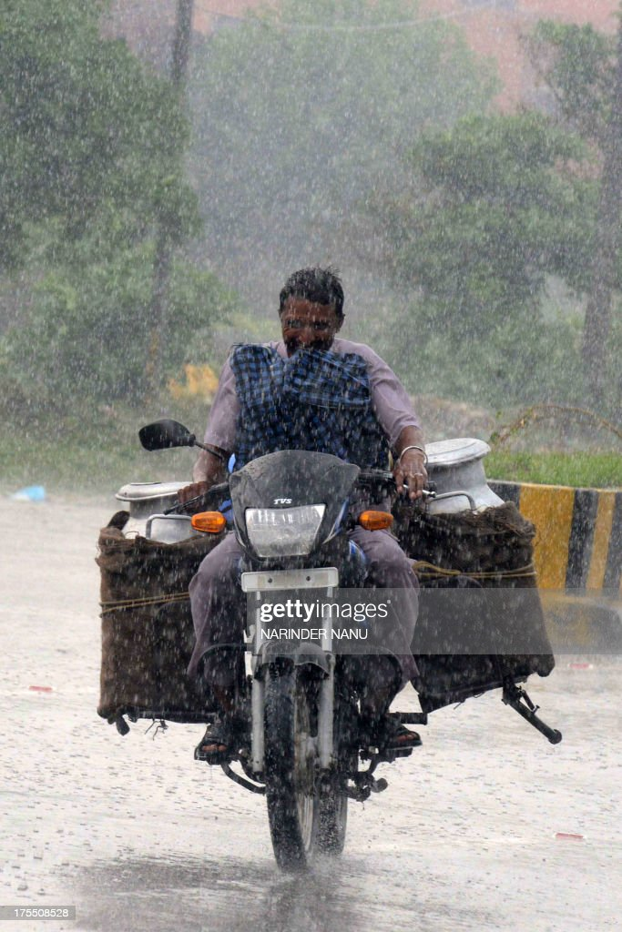 An Indian motorcyclist laden with milk churns rides through a downpour in Amritsar on August 4, 2013. Heavy rains, which fell in several areas of northern India, have brought respite to the scorching heat which has dominated life in the northern plains in previous days.