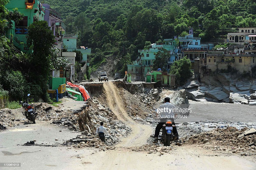 An Indian motorcyclist looks at a stretch of damaged road alongside the Mandakini river at Silli, in the flood affected area of northern Uttarakhand state on July 1, 2013. Construction along river banks will be banned in a devastated north Indian state amid concerns unchecked development fuelled last month's flash floods and landslides that killed thousands, the state's top official said July 1.