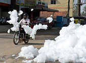 An Indian motorcyclist negotiates away from fluffy piles of foam at Varthur Kodi junction situated in east Bangalore on May 1 2015 The...