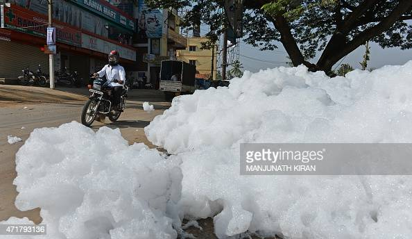 An Indian motorcyclist negotiates away from fluffy piles of foam at Varthur Kodi junction in east Bangalore on May 1 2015 The innocuouslooking foam...