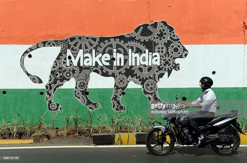 An Indian motorist rides past a wall bearing the image of the mascot for 'Make in India Week' in Mumbai on February 12, 2016. Over 190 companies, and 5,000 delegates from 60 countries, are due to take part in the first 'Make in India' week to be held in Mumbai from February 13-18. AFP PHOTO / INDRANIL MUKHERJEE / AFP / INDRANIL MUKHERJEE