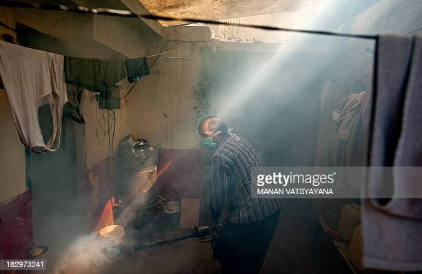 An Indian Municipal health worker fumigates against mosquitoes inside a house in a neighborhood of New Delhi on October 3 2013 As Delhi sees a spurt...