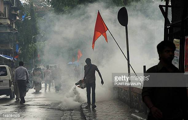 An Indian municipal worker carries a fumigation machine in a residential area during an antimalaria awareness drive in Mumbai on July 26 2012...