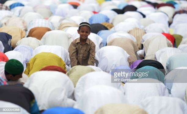 An Indian Muslim boy offers prayers on the last congregational Friday prayers of the holy month of Ramadan on a street outside the Jama Masjid in...