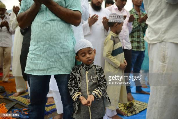 An Indian Muslim boy rests on his father as he attends prayers during Eid alFitr outside the Bandra railway station in Mumbai on June 26 2017 Muslims...