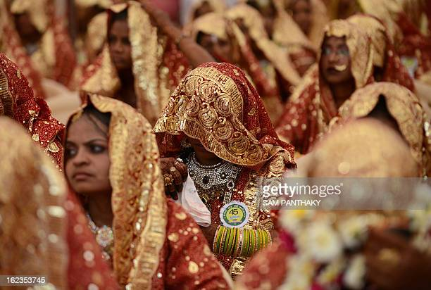 An Indian Muslim bride has her face covered with her wedding sari during a mass wedding ceremony at the ancient Sarkhej Roja in Ahmedabad on February...