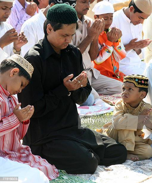 An Indian Muslim child watches as his father and other worshippers attend the last prayer of the fasting month of Ramadan at Kanchenjungha Stadium in...