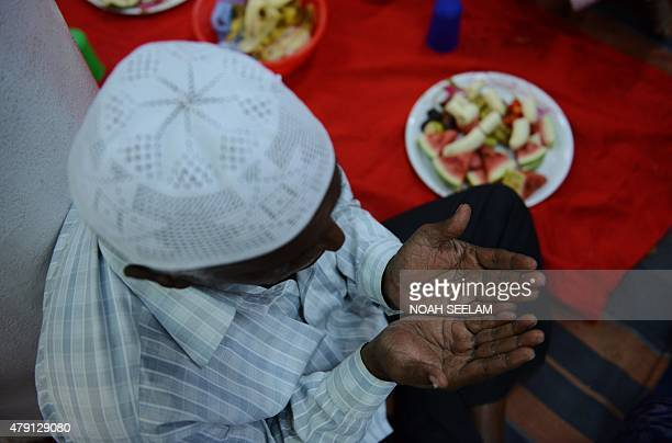 An Indian Muslim devotee offers prayers before breaking the Ramadan fast with Iftar at the MasjidESyednaOmar Farooq in Hyderabad on July 1 2015...
