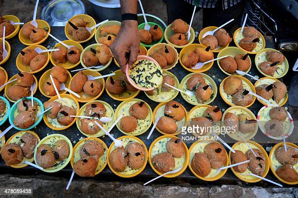 An Indian Muslim devotee prepares food prior to breaking fast on the Islamic holy month of Ramadan at the JamaeMasjid Aiwan in Hyderabad on June 22...