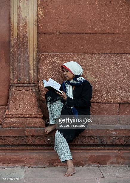 An Indian Muslim devotee reads from the Quran in the courtyard of the Jama Masjid during the Islamic holy month of Ramadan in New Delhi on July 6...