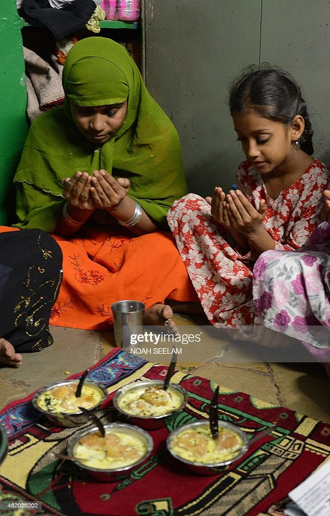 An Indian Muslim family offers prayers prior to breaking their fast in their home during the holy month of Ramadan in Hyderabad on July 11, 2014. Like millions of Muslim around the world, Indian Muslims celebrated the month of Ramadan by abstaining from eating, drinking, and smoking as well as sexual activities from dawn to dusk. AFP PHOTO/ Noah SEELAM