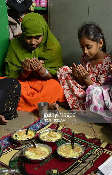 An Indian Muslim family offers prayers prior to breaking their fast in their home during the holy month of Ramadan in Hyderabad on July 11 2014 Like...