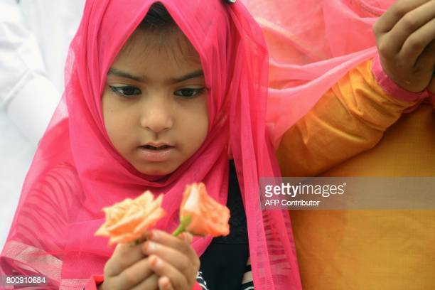 An Indian Muslim girl attends prayers during Eid alFitr outside the Bandra railway station in Mumbai on June 26 2017 Muslims around the world are...