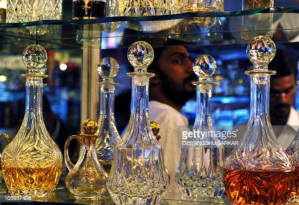 An Indian Muslim man checks the bottles of the traditional oil based perfume 'attar' as the display cabinet mirror reflect his face in a shop near a...