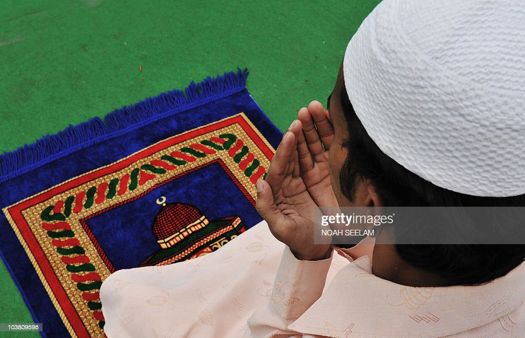 An Indian Muslim man offers Jummat-Ul-Vida prayers on the last Friday of Ramadan outside the historic Mecca Masjid in Hyderabad on September 3, 2010, ahead of the Eid al-Fitr festival.The three-day festival, which begins after the sighting of a new crescent moon, marks the end of the Muslim fasting month of Ramadan, during which devout Muslims abstain from food, drink, smoking and sex from dawn to dusk. AFP PHOTO/Noah SEELAM