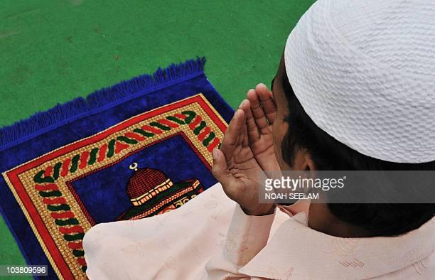 An Indian Muslim man offers JummatUlVida prayers on the last Friday of Ramadan outside the historic Mecca Masjid in Hyderabad on September 3 ahead of...